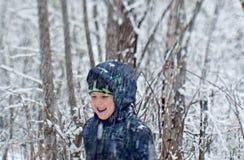有使用在雪森林里的铁锹的男孩 库存图片