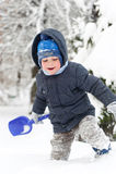 有使用在雪的铁锹的小男孩 库存图片