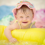 有使用在水池的下来综合症状的快乐的女婴 免版税库存图片