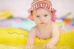 有使用在水池的下来综合症状的快乐的矮小的女婴 库存照片