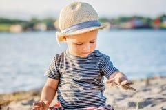 有使用在bea的沙子的夏天帽子的一个逗人喜爱的小男孩 免版税库存图片