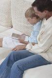 有使用数字式片剂的儿子的父亲 库存图片