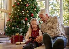 有使用数字式片剂的孙女的老人在基督期间 库存图片