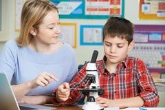 有使用显微镜的男学生的老师在科学类 库存照片