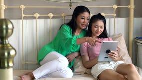 有使用片剂的女儿的可爱的美丽的母亲演奏g 库存图片