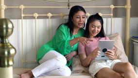 有使用片剂的女儿的可爱的美丽的母亲演奏g 库存照片