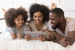 有使用片剂的女儿的愉快的非洲父母说谎在床上 免版税库存照片