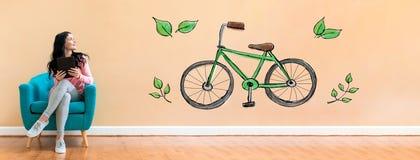 有使用片剂的妇女的Eco自行车 库存照片