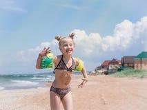 有使用由海的美好的发型乐趣的女孩在一个晴天 免版税库存照片