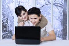 有使用膝上型计算机的丈夫的妇女 库存照片