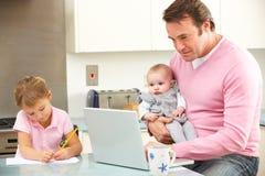有使用膝上型计算机的子项的父亲在厨房 免版税库存图片