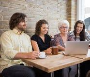 有使用膝上型计算机的朋友的妇女在咖啡馆表 图库摄影