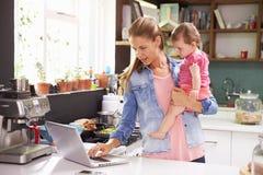 有使用膝上型计算机的年轻女儿的母亲在厨房 库存图片