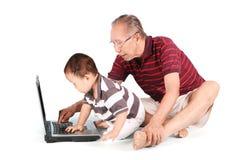 有使用膝上型计算机的婴孩的祖父 免版税库存图片