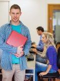 有使用计算机的年轻大学生的老师在计算机室 免版税图库摄影