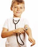 有使用象成人行业医生关闭微笑的听诊器的小逗人喜爱的男孩隔绝在白色 库存图片