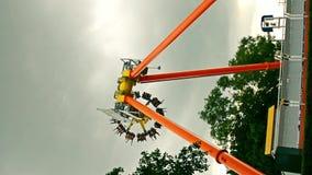 有使用以兴奋的人的可怕巨型金属轮子摇摆摆锤在有黑暗的多云天空雷暴的一个游乐园 股票录像