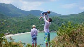 有使用以海和山为背景的两个孩子的一个年轻人 股票视频