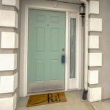 有侧灯的清楚的正方形绿色大门在家门面被观看反对多云天空 图库摄影