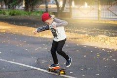 有便士滑板的小都市男孩 在Th的小孩骑马 免版税库存照片