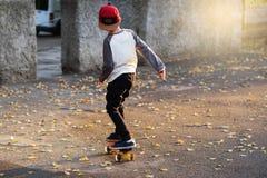有便士滑板的小都市男孩 在Th的小孩骑马 库存图片