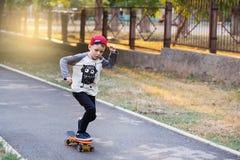 有便士滑板的小都市男孩 在Th的小孩骑马 免版税库存图片