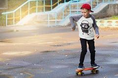 有便士滑板的小都市男孩 在Th的小孩骑马 库存照片