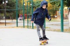 有便士滑板的小都市男孩 滑冰在autu的孩子 免版税库存照片