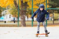 有便士滑板的小都市男孩 滑冰在autu的孩子 库存图片
