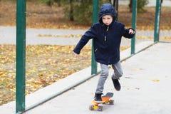 有便士滑板的小都市男孩 滑冰在autu的孩子 库存照片