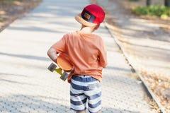 有便士滑板的小都市男孩 滑冰在summe的孩子 库存照片