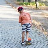有便士滑板的小都市男孩 滑冰在summe的孩子 免版税库存照片