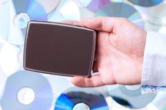 有便携式的盘的人的手在CD的背景 免版税库存图片