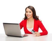 有便携式计算机和信用卡的愉快的妇女 库存图片