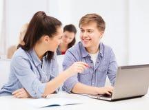 有便携式计算机的两名微笑的学生 库存图片