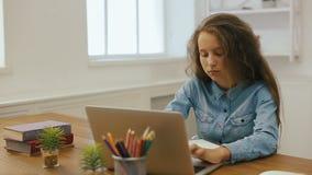 有便携式计算机的女孩做着家庭作业 大学教育 在家学习和使用个人计算机的疲乏的女学生 股票录像