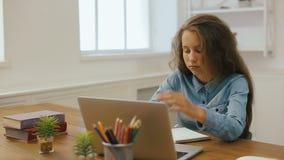 有便携式计算机的女孩做着家庭作业 大学教育 在家学习和使用个人计算机的疲乏的女学生 影视素材