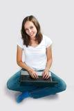 有便携式计算机的学生女孩在灰色背景 免版税库存图片