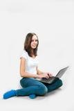 有便携式计算机的学生女孩在灰色背景 库存图片