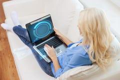 有便携式计算机的微笑的妇女在家 免版税库存图片