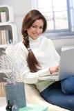 有便携式计算机的微笑的妇女 免版税图库摄影