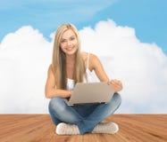 有便携式计算机的愉快的学生女孩 免版税库存图片