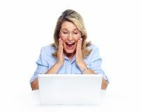 有便携式计算机的愉快的资深妇女。 免版税库存图片