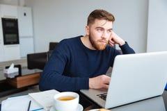 有便携式计算机的沉思人在家 库存图片