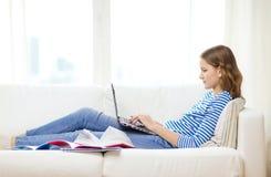 有便携式计算机的繁忙的十几岁的女孩在家 库存照片
