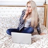 有便携式计算机的迷人的年轻白肤金发的妇女坐床 库存图片