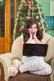 有便携式计算机的震惊妇女坐扶手椅子 免版税库存图片