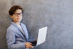 有便携式计算机的青少年的男孩由墙壁 免版税库存照片