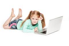 有便携式计算机的滑稽的小女孩 免版税图库摄影