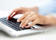有便携式计算机键盘的手。 库存照片